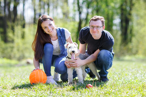 Happy couple with dog in park